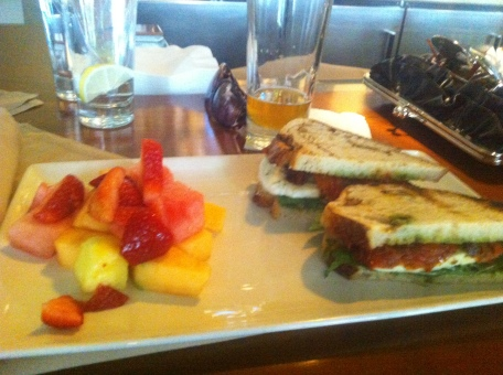Caprese Sandwich - La Brea Bread grilled with olive oil topped with fresh mozzarella cheese, roasted tomatoes, tomato-caper spread and pesto with a side of fruit