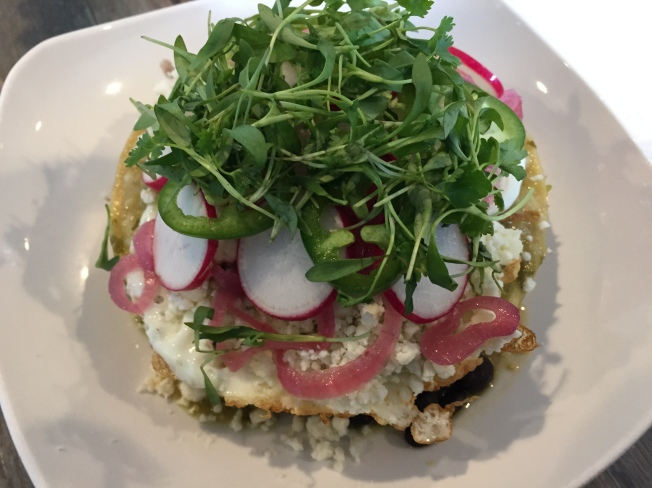 Tostada Chilaquiles - with tomatilla salsa, fried eggs, black beans, housemade queso fresco, pickled onion, radish, jalapeno, microcilantro - $11 (add pork $2)