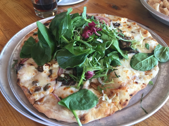 Fun-Guy - seasonal mushroom medley, garlic, torn basil, red onion, feta, mozzarella, nutmeg bechamel sauce, topped with seasonal greens - $9.50