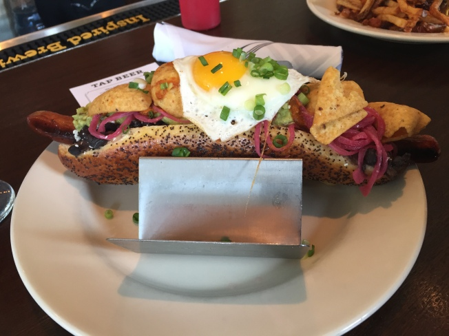 Huevos Rancheros Dog - 10 black bean, cotija, avocado, salsa roja, pickled onion, fried egg, corn chips
